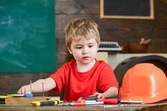 Kid boy play as handyman. Childhood concept. Toddler on busy face plays with tools at home in workshop. Child cute and Royalty Free Stock Photos