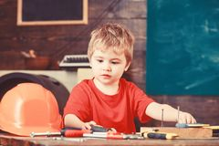Kid boy play as handyman. Childhood concept. Toddler on busy face plays with tools at home in workshop. Child cute and royalty free stock photo