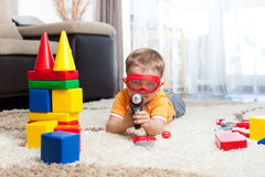Kid boy playing with building blocks and imagining himself a hero Royalty Free Stock Images