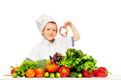 Kid boy playing chef cook preparing fresh salad Royalty Free Stock Photos