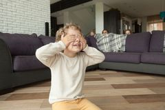 Kid boy playing hide and seek with family at home. Kid boy playing hide and seek game at home, child closing eyes with hands counting while parents and sister Royalty Free Stock Images