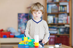 Kid boy playing with lots of colorful plastic blocks indoor Stock Images