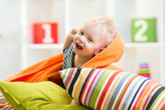 Kid boy playing on pillows in bedroom Stock Photos