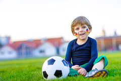 Kid boy playing soccer with football Stock Image