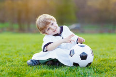 Kid boy playing soccer with football Royalty Free Stock Images