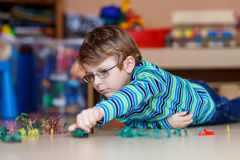 Kid boy playing with toy soldiers indoors at Stock Photo