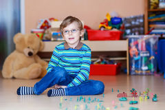 Kid boy playing with toy soldiers indoors at Stock Photography