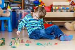 Kid boy playing with toy soldiers indoors at Stock Photos