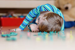 Kid boy playing with toy soldiers indoors at Royalty Free Stock Image