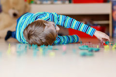 Kid boy playing with toy soldiers indoors at Royalty Free Stock Images