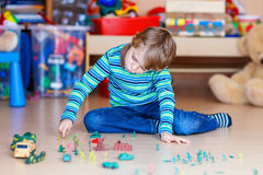 Kid boy playing with toy soldiers indoors at Royalty Free Stock Photos