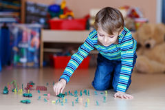 Kid boy playing with toy soldiers indoors at Royalty Free Stock Photography