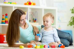 Kid boy playing toys together mother Royalty Free Stock Images