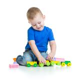 Kid boy playing with train toy sitting. On white background Stock Photos