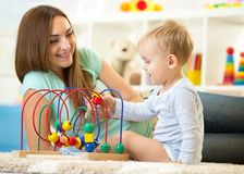 Kid boy plays with educational toy indoor. Happy. Kid boy plays with educational toy in nursery at home. Happy mother looking at her smart son Royalty Free Stock Photo