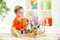 Kid boy plays with educational toy indoor Stock Photography