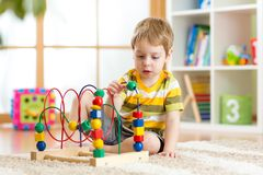 Kid boy plays with educational toy indoor Stock Images