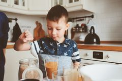 Kid boy preparing dough for muffins in cozy modern white kitchen. Kids cooking at home Stock Image