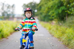 Kid boy in red safety helmet driving on his first Stock Photography