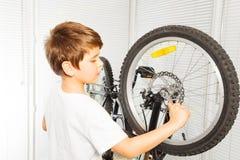 Kid boy repairing his bicycle at garage Royalty Free Stock Image