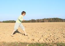 Kid - boy running on field. Little kid - barefoot boy running on ground of dried field stock photography