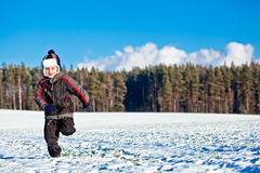 Kid boy running in winter Royalty Free Stock Photos