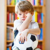 Kid boy sad about lost football or soccer game Stock Photos