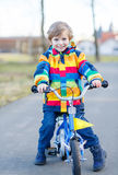 Kid boy in safety helmet and colorful raincoat riding bike Royalty Free Stock Images