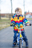 Kid boy in safety helmet and colorful raincoat riding bike Stock Photos