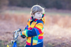 Kid boy in safety helmet and colorful raincoat riding bike, outd Royalty Free Stock Photos