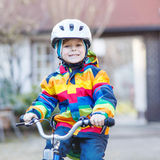 Kid boy in safety helmet and colorful raincoat riding bike, outd Stock Image