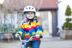 Kid boy in safety helmet and colorful raincoat riding bike, outd Royalty Free Stock Image