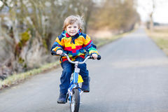 Kid boy in safety helmet and colorful raincoat riding bike, outd. Funny cute  preschool kid boy in colorful raincoat riding his first bike and having fun on warm Royalty Free Stock Image
