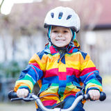 Kid boy in safety helmet and colorful raincoat riding bike, outd Stock Images