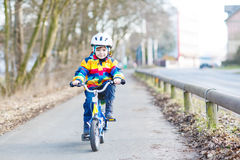 Kid boy in safety helmet and colorful raincoat riding bike, outd Royalty Free Stock Photography