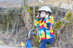 Kid boy in safety helmet and colorful raincoat riding bike, outd Royalty Free Stock Images