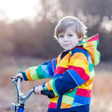 Kid boy in safety helmet and colorful raincoat riding bike, outd Stock Photography