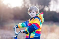 Kid boy in safety helmet and colorful raincoat riding bike, outd Stock Photos
