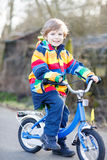 Kid boy in safety helmet and colorful raincoat riding bike, outd Stock Photo