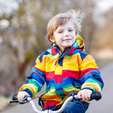Kid boy in safety helmet and colorful raincoat riding bike Stock Images