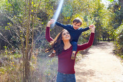 Kid boy sit on mother shoulders walking park Stock Image