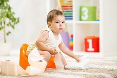 Kid boy sitting on chamber pot with toilet paper Royalty Free Stock Photo