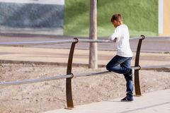 Kid boy standing alone on the bridge and looking down to the water stock photo