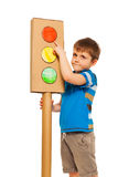 Kid boy studying traffic light rules. Boy studying road traffic rules, pointing to the red light of cardboard lights model, isolated on white Stock Photo