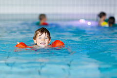 Kid boy with swimmies learning to swim in an indoor pool Stock Photo