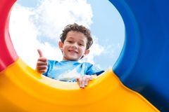 Kid boy thumbs up and having fun to play on children`s climbing Stock Image