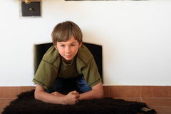 Kid - boy under the furnace Stock Image