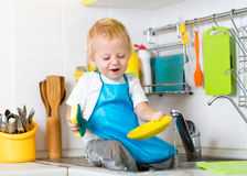 Kid boy washing dishes and having fun in the Royalty Free Stock Photo