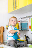 Kid boy washing dishes and having fun in the Royalty Free Stock Images