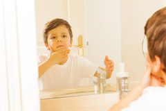 Kid boy washing his face and looking in the miror Stock Images